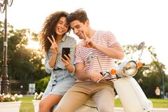 Portret mężczyzna i kobieta jest ubranym słuchawki ono uśmiecha się przy smartphone podczas gdy siedzący na hulajnodze wpólnie na zdjęcia royalty free