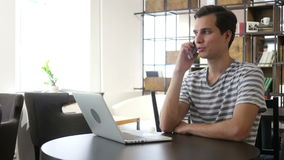 Portret mężczyzna mówienie na telefonie komórkowym, siedzący przy biurkiem, patrzeje laptop zbiory wideo