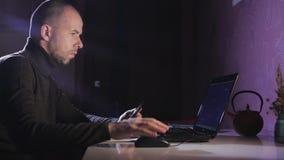 Portret mężczyzna na jego laptopie przy nocą z twarzą koncentracja zdjęcie wideo