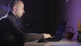 Portret mężczyzna na jego laptopie przy nocą z twarzą koncentracja zbiory