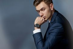 Portret mężczyzna obsiadanie z kostiumem z zegarkiem, studio obrazy royalty free