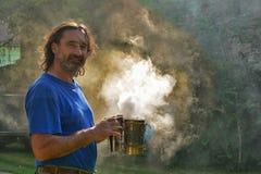 Portret mężczyzna otaczający dymem przeciw ranku światłu słonecznemu Zdjęcie Stock