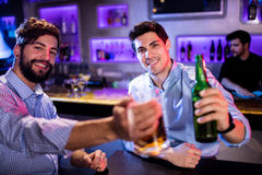 Portret mężczyzna pokazuje szkło piwna i piwna butelka Zdjęcie Royalty Free