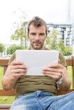 Portret mężczyzna przyglądająca wiadomość w pastylka komputerze, plenerowy obraz royalty free