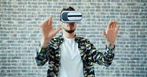 Portret mężczyzna używa rzeczywistość wirtualna szkła rusza się ręki na ceglanym tle zbiory wideo