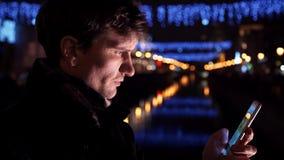 Portret mężczyzna używa smartphone stoi samotnego outdoors przy nocą na miasto ulicie zbiory