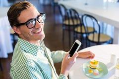 Portret mężczyzna używa telefon komórkowego podczas gdy mieć lunch fotografia stock