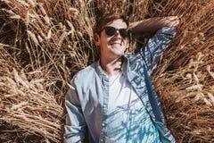 Portret mężczyzna w pszenicznym polu, facet z szkłami i nakrętka w stylu mody, zdjęcie stock