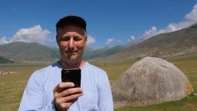 Portret mężczyzna wyszukuje telefon w nakrętce z dużym kamieniem behind górami i zbiory