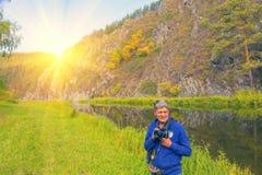 Portret mężczyzna z kamerą w jego rękach na tle opposite skalisty brzeg obrazy royalty free