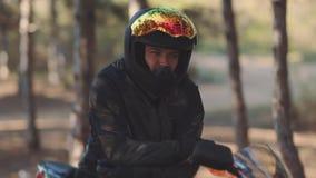 Portret mężczyzny motocyklista w czarnym hełmie przy zmierzchem Rowerzysta w lesie, koloru naliczek zdjęcie wideo