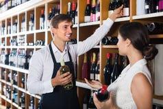 Portret męska sprzedawcy seansu butelka wino żeński zwyczaj Zdjęcie Royalty Free