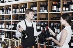 Portret męska sprzedawcy seansu butelka wino żeński zwyczaj Fotografia Royalty Free