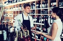 Portret męska sprzedawcy seansu butelka wino żeński zwyczaj Fotografia Stock