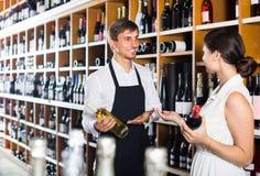 Portret męska sprzedawcy seansu butelka wino żeński zwyczaj Obraz Stock
