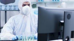 Portret męski naukowiec w białych coveralls pracuje na pececie zbiory wideo