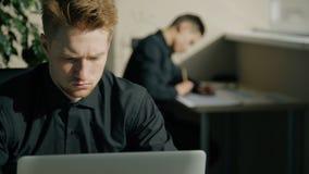 Portret męski offce pracownik patrzeje laptop w nowożytnym biurze z jego kolegą zdjęcie wideo