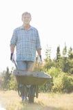 Portret męski ogrodniczki dosunięcia wheelbarrow przy ogródem Obrazy Stock