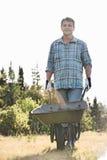 Portret męski ogrodniczki dosunięcia wheelbarrow przy ogródem Fotografia Royalty Free
