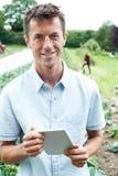 Portret Męski Rolniczy pracownik Używa Cyfrowej pastylkę W Fie fotografia stock