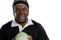 Portret męski rugby gracz jest ubranym mouthguard mienia rugby białą piłkę fotografia royalty free