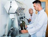 Portret męski wytwórnia win pracownik z rozlewniczą maszynerią na fabryce Obrazy Royalty Free