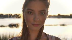 Portret młoda ładna kobieta patrzeje w, zmierzch, obiektyw, i migoczemy, rzeki i natury tło, zbiory