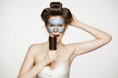 Portret młoda śmieszna dziewczyna w włosianych curlers i twarzowy maskowy śpiew w grępli nad białym tłem Piękno i skincare Fotografia Royalty Free