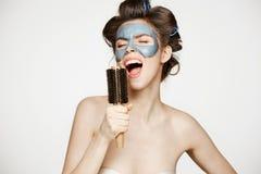 Portret młoda śmieszna dziewczyna w włosianych curlers i twarzowy maskowy śpiew w grępli nad białym tłem Piękno i skincare Zdjęcia Stock