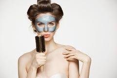Portret młoda śmieszna dziewczyna w włosianych curlers i twarzowy maskowy śpiew w grępli nad białym tłem Piękno i skincare Obrazy Stock