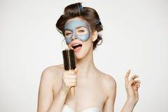Portret młoda śmieszna dziewczyna w włosianych curlers i twarzowy maskowy śpiew w grępli nad białym tłem Piękno i skincare Fotografia Stock