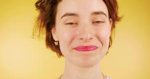 Portret młoda, świeża brunetki dziewczyna patrzeje szczęśliwie z czerwonymi wargami i zbiory wideo