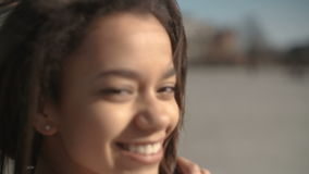 Portret młoda amerykanin afrykańskiego pochodzenia kobieta pozuje kamera, outdoors zbiory
