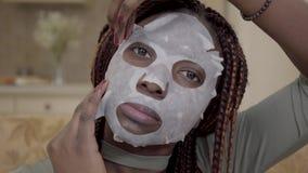 Portret młoda amerykanin afrykańskiego pochodzenia kobieta stosuje odmładzanie twarzową maskę na jej twarzy zamkniętej w górę w d zbiory