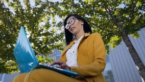 Portret młoda atrakcyjna biznesowa kobieta używa laptop na przerwie outdoors, piękny żeńskiego ucznia obsiadanie na zbiory wideo