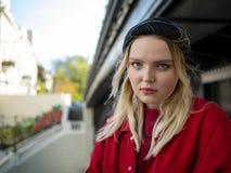 Portret młoda atrakcyjna dziewczyna w czerwonej kurtce i dziającej czarnej kurtce pod mostem z poważną twarzą obrazy stock