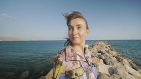 Portret młoda atrakcyjna kobieta ono uśmiecha się na kamiennym dennego wybrzeża tle Włosy trzepocze w wiatrze zdjęcie wideo
