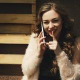 Portret młoda atrakcyjna kobieta opowiada telefonem i pokazuje cisza gest zdjęcie stock