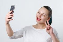 Portret m?oda atrakcyjna kobieta robi selfie fotografii na smartphone na bielu obrazy royalty free