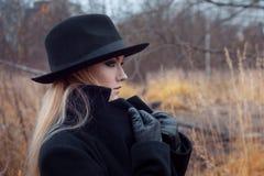 Portret młoda atrakcyjna kobieta w czarnym kapeluszu i żakiecie Dźwignięcie kołnierza żakiet Jesień krajobraz, sucha trawa Obrazy Stock