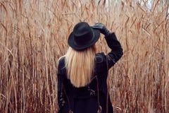 Portret młoda atrakcyjna kobieta w czarnym kapeluszu i żakiecie Jesień krajobraz, sucha trawa spójrz z powrotem Trzymać kapeluszo Zdjęcia Stock