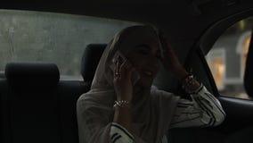 Portret młoda, atrakcyjna muzułmańska kobieta dojeżdżać do pracy w samochodzie, Jest ubranym chustki na głowę obsiadanie na tylny zbiory