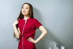Portret młoda Azjatycka kobieta w mundurze na popielatym tle zdjęcia stock