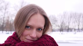 Portret młoda błękitnooka dosyć ono uśmiecha się kobieta patrzeje w kamerę w zimy miasta parku który i ono zawija zdjęcie wideo