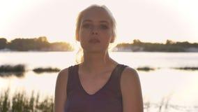 Portret młoda blond kobieta patrzeje w kamerze, wzruszający włosy, ono uśmiecha się, zmierzch i obiektyw, migoczemy, rzeka i natu zdjęcie wideo