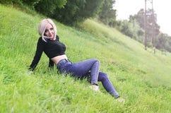 Portret młoda blond kobieta z krótkiego włosy obsiadaniem na gre obraz stock
