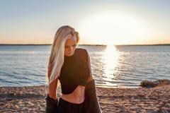 Portret młoda blond zmysłowa sportowa sprawności fizycznej kobieta z zmierzchem na tle i światłem słonecznym w jej włosy obrazy royalty free