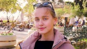 Portret młoda blondynki dziewczyna z długie włosy jest siedzący w miejscu publicznym w parku i ono uśmiecha się przy kamerą od zdjęcie wideo