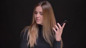 Portret młoda caucasian długowłosa blondynki dziewczyna słucha muzyczny używa smartphone i słuchawki na czerni zdjęcie wideo