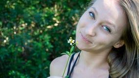 Portret młoda caucasian normalna blondynki kobiety twarz z błękitnymi zielonymi oczami ono uśmiecha się z stokrotka kwiatem w nat obraz royalty free